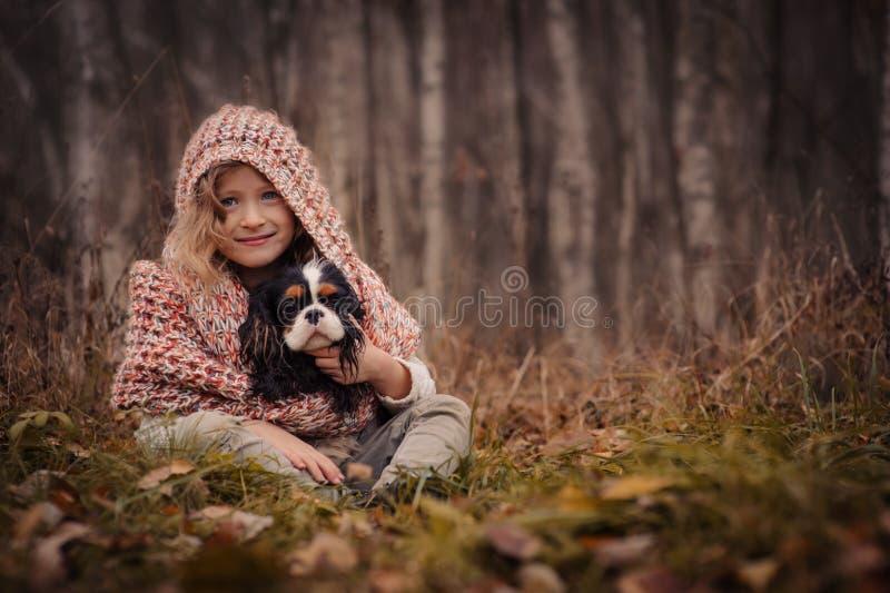 Den gulliga lyckliga ungeflickan med hennes hund på hemtrevlig höst går i skog royaltyfria foton