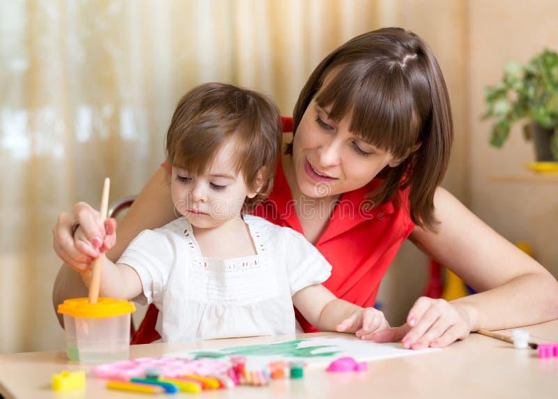 Den gulliga modern undervisar hennes dotterunge att måla royaltyfria foton