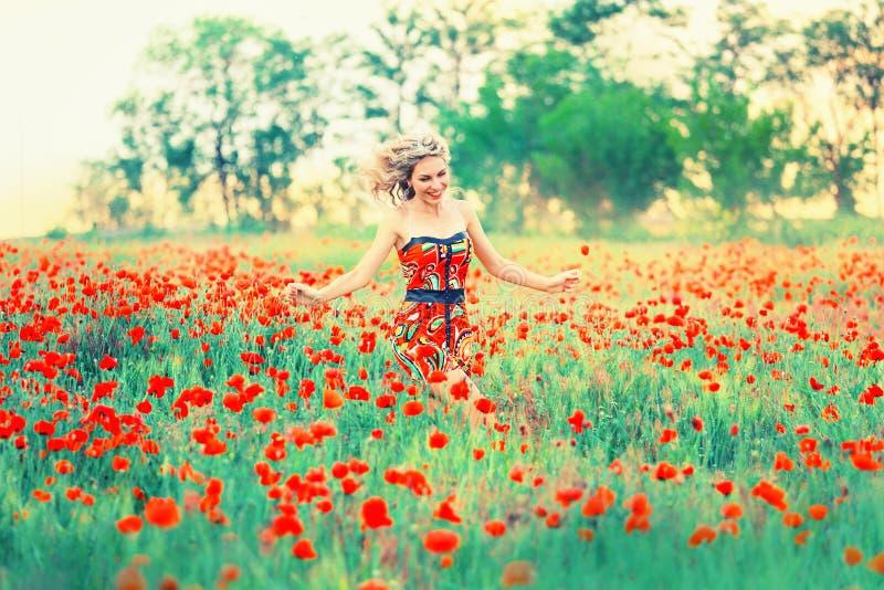 Den gulliga nätta damen med blont hår i en kort klänning spelar i ett brett vallmofält, som om i barndom, körningar och danser fotografering för bildbyråer