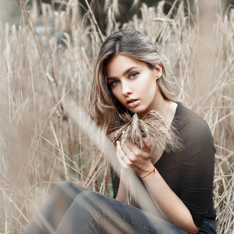 Den gulliga nätta lantliga unga kvinnan med runda ögon i en svart t-skjorta för tappning i moderiktig jeans vilar att sitta utomh arkivbilder
