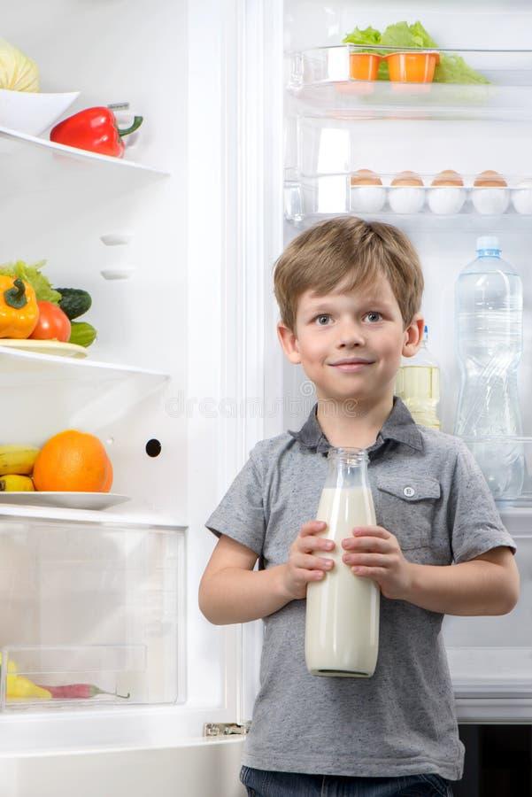 Den gulliga pojkeinnehavflaskan av mjölkar nära den öppna kylen arkivfoton