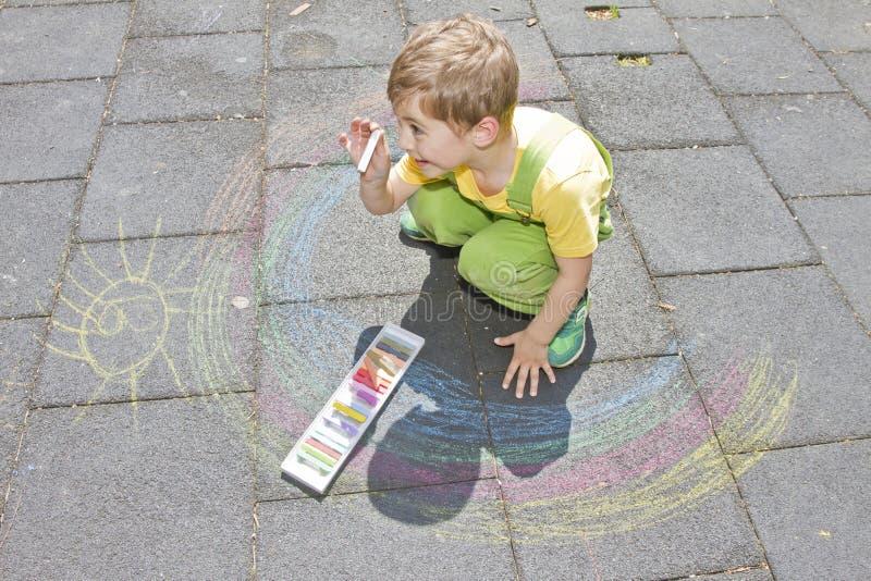 Den gulliga pojken drar med färgrika chalks på asfalt Sommaraktivitet och idérika lekar för små ungar Barn som har tillsammans gy arkivbilder