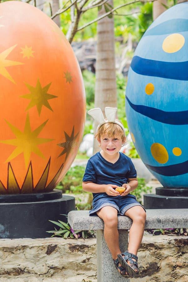 Den gulliga pojken för den lilla ungen med kaninöron som har gyckel med traditionella påskägg, jagar, utomhus Fira påskferie Lite royaltyfri foto