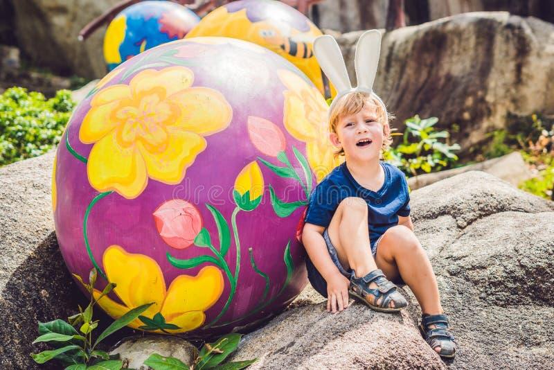 Den gulliga pojken för den lilla ungen med kaninöron som har gyckel med traditionella påskägg, jagar, utomhus Fira påskferie Lite arkivbild