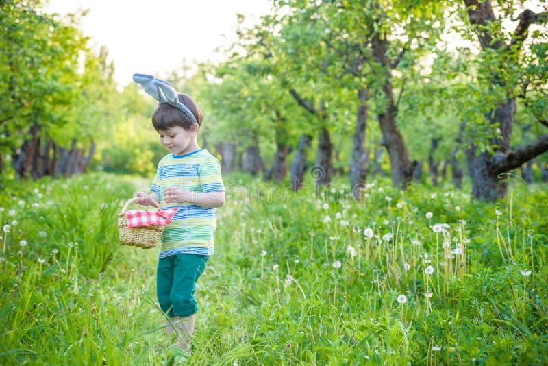 Den gulliga pojken för den lilla ungen med kaninöron som har gyckel med traditionella påskägg, jagar royaltyfria bilder