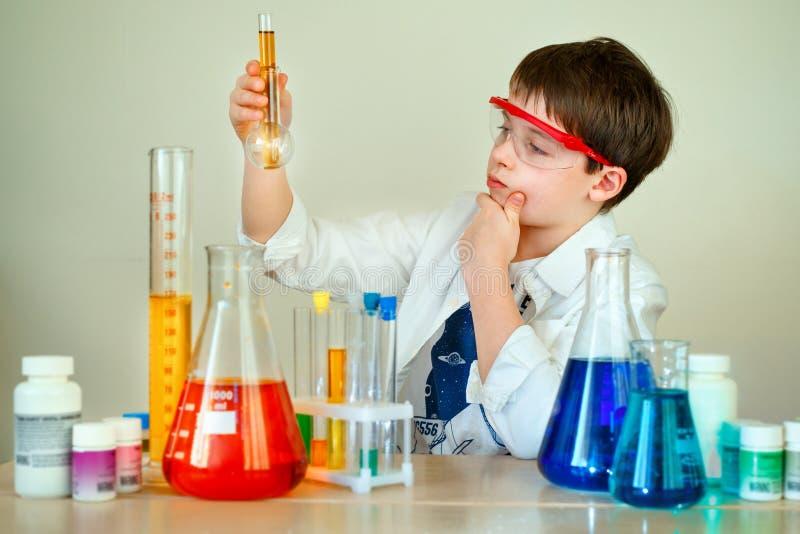 Den gulliga pojken gör vetenskapsexperiment i ett laboratorium royaltyfri foto