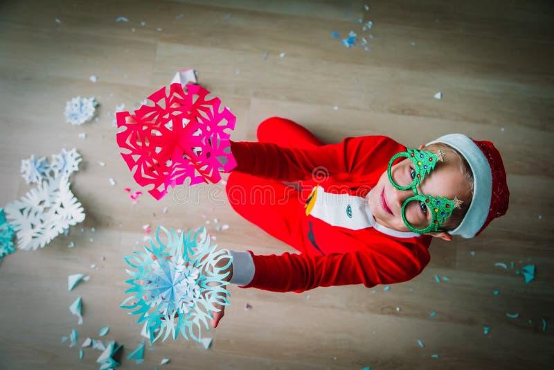 Den gulliga pojken klippte snöflingor för julberöm royaltyfria foton