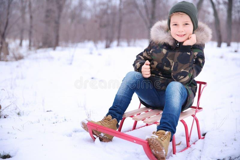 Den gulliga pojken med släden i snöig parkerar arkivbilder