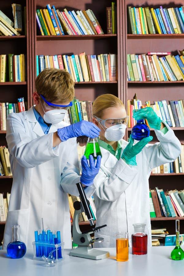 Den gulliga pojken och flickan som gör biokemi, forskar in royaltyfri foto