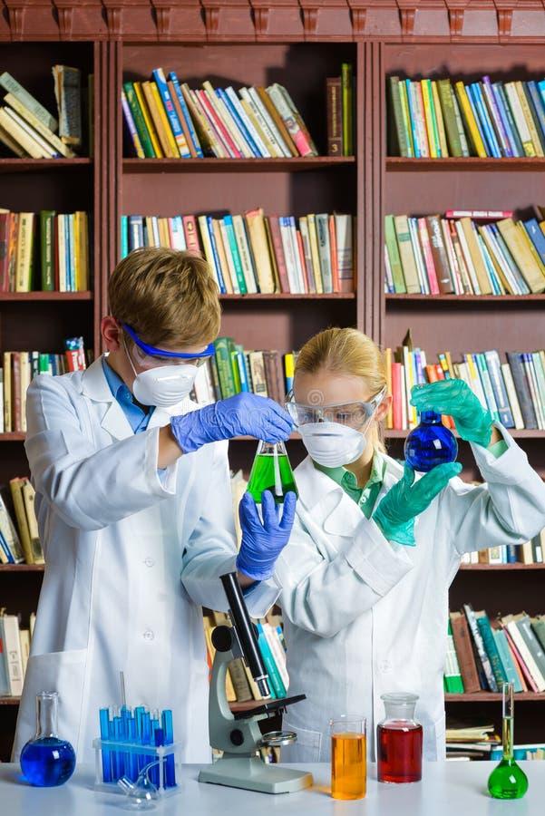 Den gulliga pojken och flickan som gör biokemi, forskar i kemigrupp royaltyfria foton