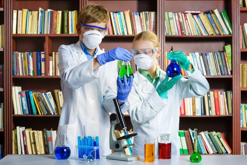 Den gulliga pojken och flickan som gör biokemi, forskar i kemigrupp royaltyfri fotografi