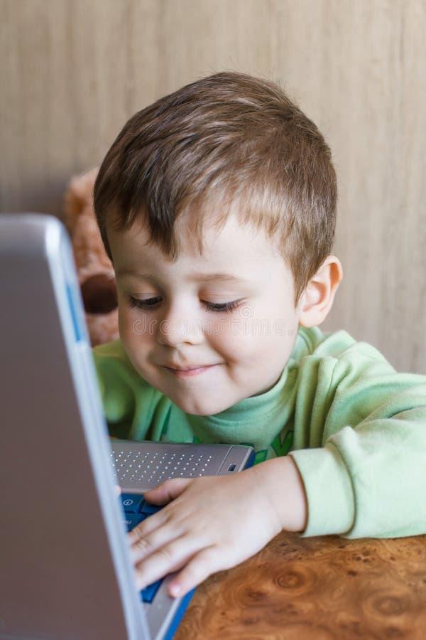 Den gulliga pojken skjuter bärbara datorer tangentbord, och han ser skärmen arkivbilder
