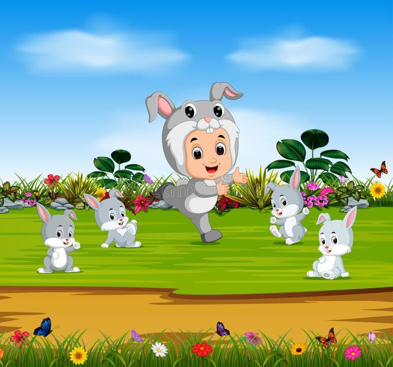 Den gulliga pojken som bär den kanindräkten och leken med kaniner stock illustrationer