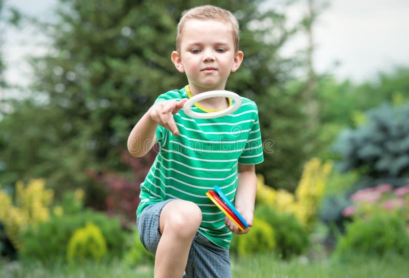 Den gulliga pojken som spelar en lek som kastar cirklar i sommar, parkerar utomhus Gl?djen av segern arkivbilder