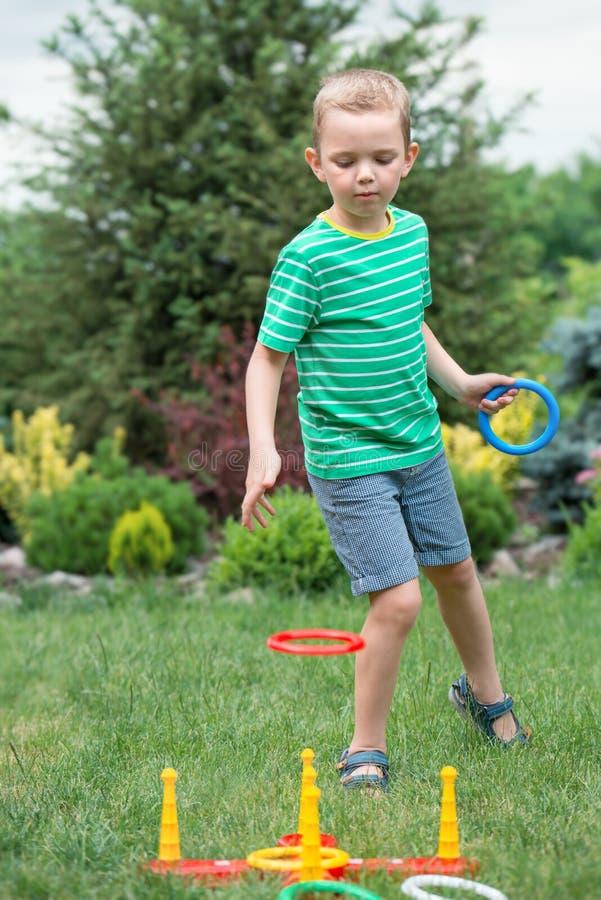 Den gulliga pojken som spelar en lek som kastar cirklar i sommar, parkerar utomhus Gl?djen av segern fotografering för bildbyråer