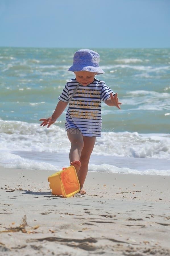 Den gulliga pojken spelar en hink på stranden arkivfoto