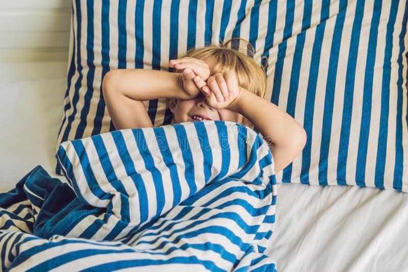 Den gulliga pojken vaknade upp i hans säng Barnsömnbegrepp royaltyfri foto