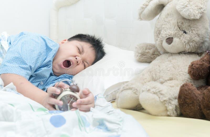 Den gulliga pojken vaknar upp och att gäspa arkivfoto