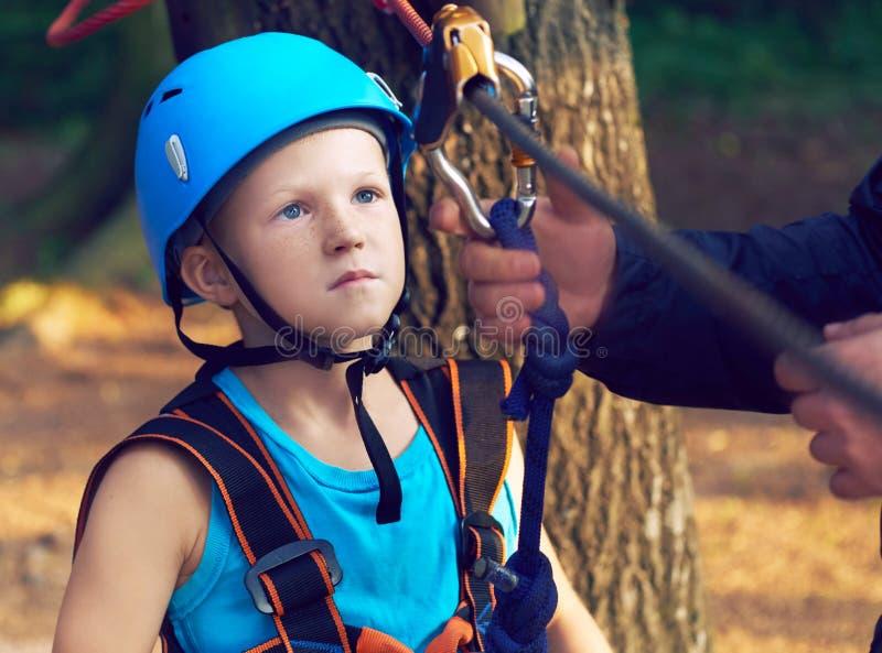 Den gulliga pysen i blå skjorta och hjälmen som har gyckel på affärsföretaget, parkerar, rymmer rep och prepering för att klättra royaltyfri foto