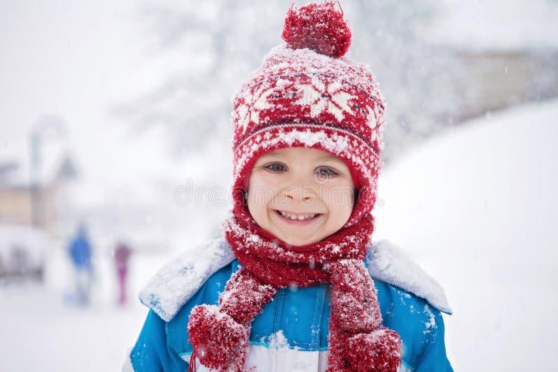 Den gulliga pysen i blått övervintrar dräkten, att spela som är utomhus- i snön arkivbild