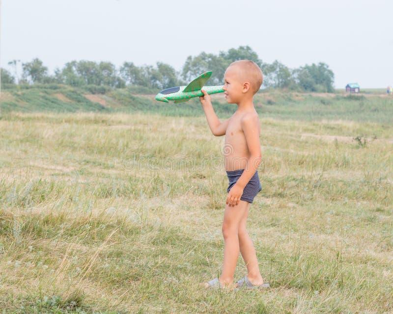 Den gulliga pysen i kortslutningar går över fältet och rymmer ett leksakflygplan i hans hand arkivfoto