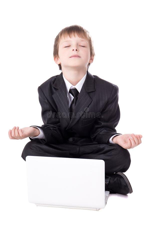 Den gulliga pysen i sammanträde för affärsdräkt i yoga poserar med lapto royaltyfria bilder