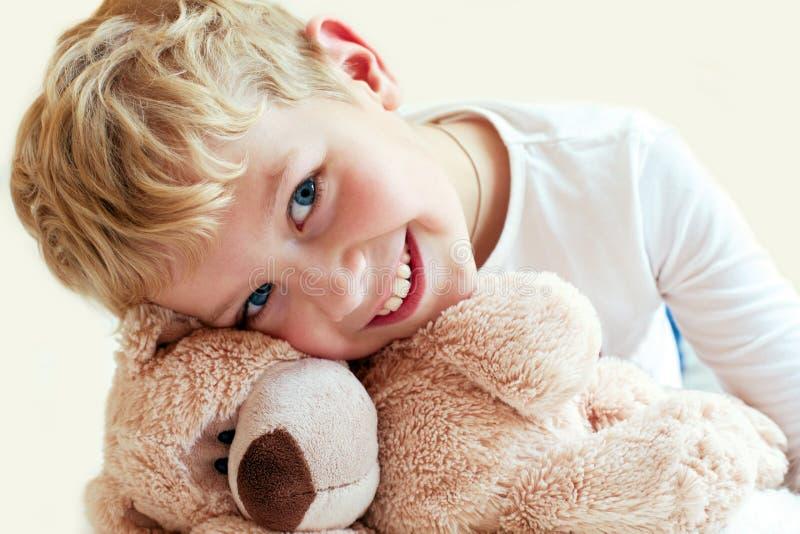Den gulliga pysen kramar hans nallebjörn arkivbilder