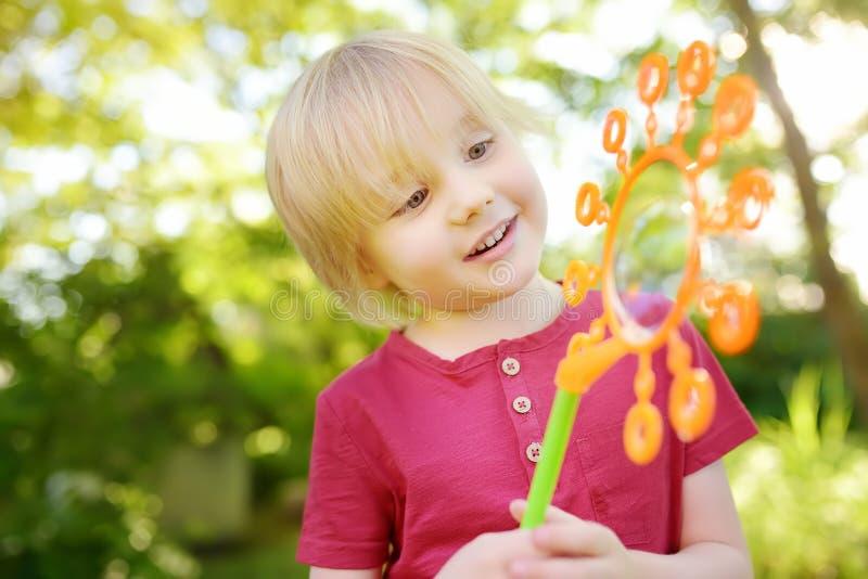 Den gulliga pysen leker med utomhus- stora bubblor Barnet blåser stora och små bubblor samtidigt royaltyfri bild