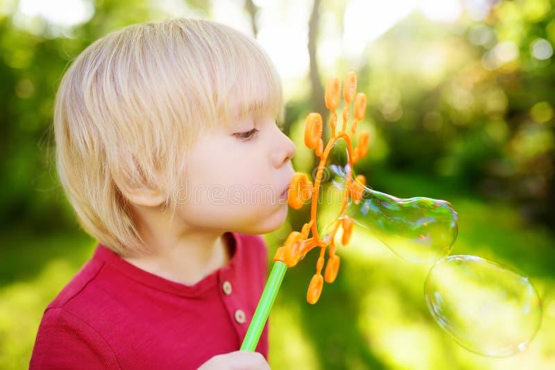Den gulliga pysen leker med utomhus- stora bubblor Barnet blåser stora och små bubblor samtidigt arkivfoto