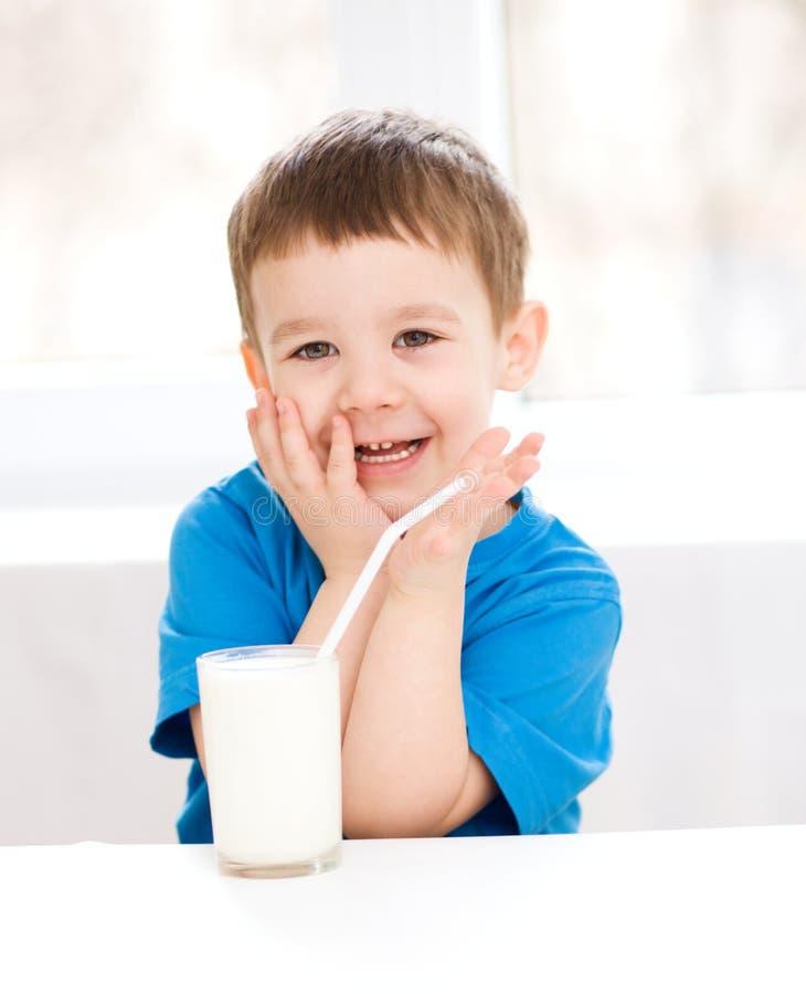 Den gulliga pysen med ett exponeringsglas av mjölkar arkivfoton