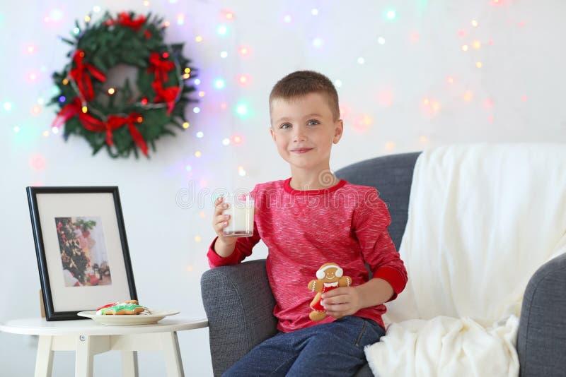 Den gulliga pysen med exponeringsglas av mjölkar och kakan i rum som dekoreras för jul arkivfoton