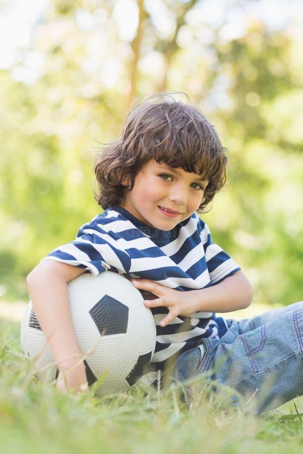 Den gulliga pysen med fotbollsammanträde på gräs parkerar in fotografering för bildbyråer