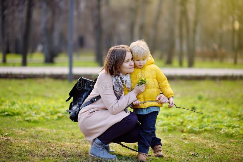 Den gulliga pysen med hans unga moder som in spelar, parkerar royaltyfri fotografi