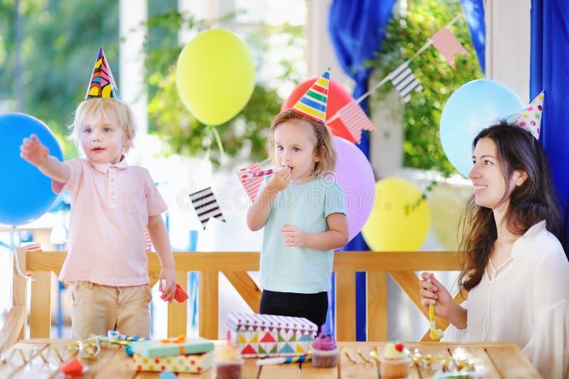 Den gulliga pysen och flickan firar födelsedagpartiet med färgrik garnering och kakor royaltyfri bild