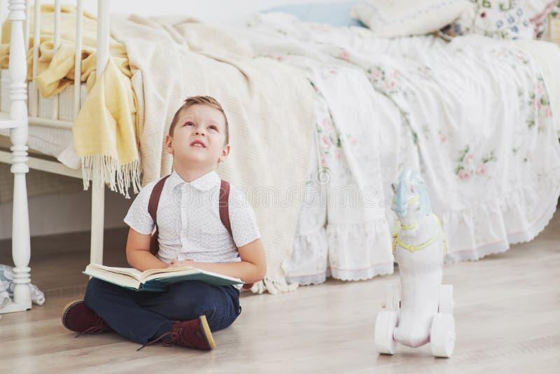 Den gulliga pysen ska skola för första gången Barn med den skolapåsen och boken Ungen gör en portfölj, barnrum royaltyfri fotografi