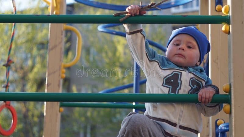 Den gulliga pysståenden i en blå hatt klättrar trappa på lekplatsen arkivbild