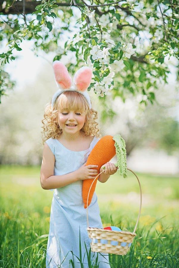 Den gulliga roliga flickan med den påskägg och kaninen gå i ax på trädgården målat gräs för 2 placerade allt för easter för hinkf royaltyfria foton