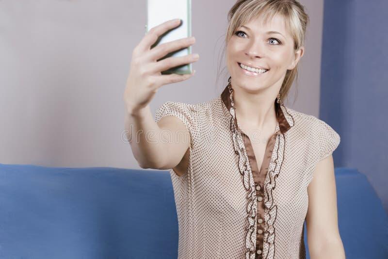 Den gulliga sexiga blonda flickan sitter på soffan Hon ser hennes smartphone och gör en selfie arkivbilder