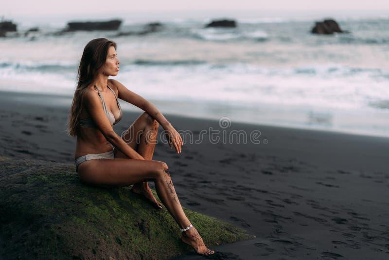 Den gulliga sexiga flickan i beige swimwear vilar p? den svarta vulkaniska sandstranden arkivbilder