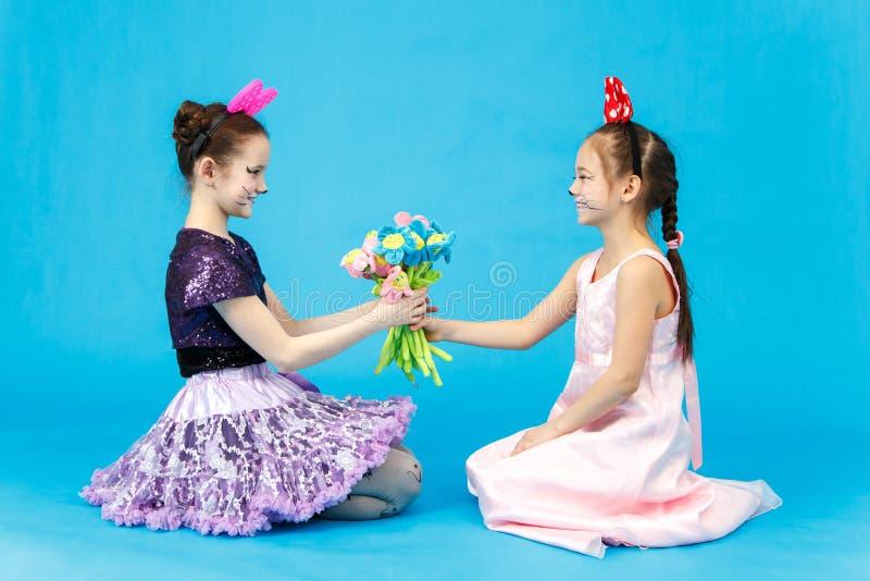Den gulliga skolflickan framlägger en bukett av blommor till hennes klasskompis royaltyfri foto