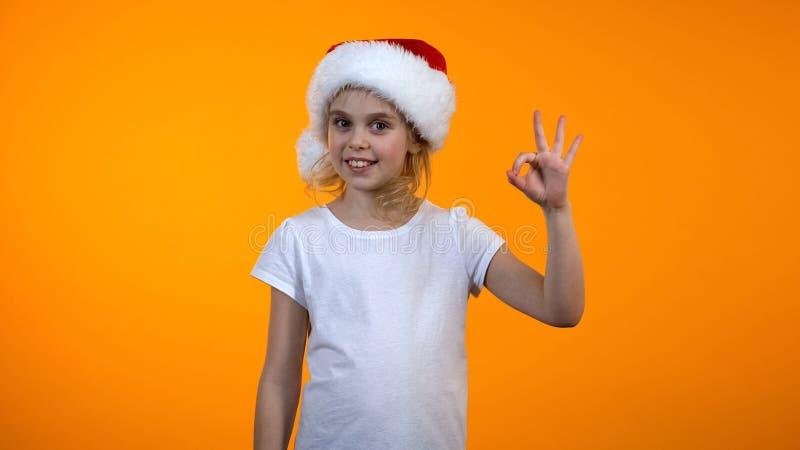 Den gulliga skolflickan i ok tecken för santa hattvisning och att le till kameran, ferie vilar arkivbild