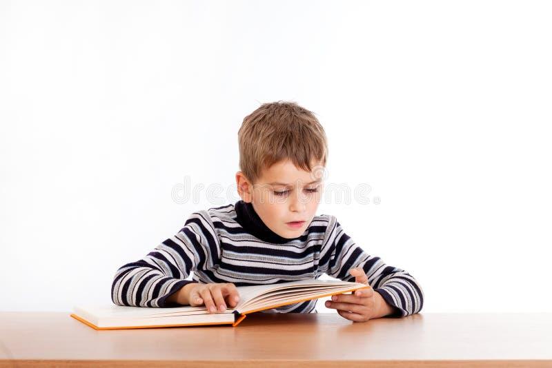 Den gulliga skolpojken läser en bok royaltyfria foton