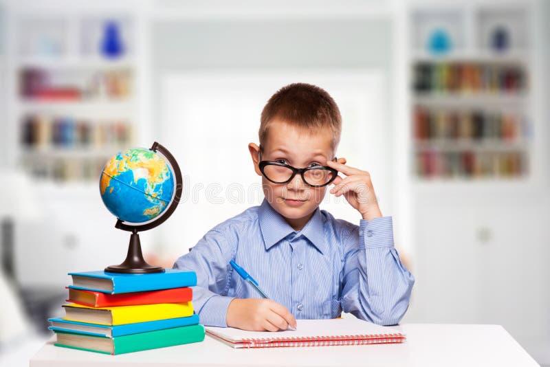 Den gulliga skolpojken skriver läxa royaltyfria bilder