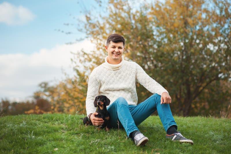 Den gulliga smarta hunden och hans unga stiliga man för ägare har gyckel i parkera, befruktningdjur, husdjur, kamratskap, samhöri royaltyfri bild