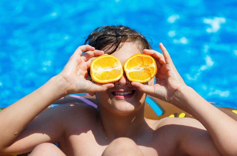 Den gulliga sportiga pojken simmar i pölen med munkcirkeln och har gyckel, leenden, hållapelsiner semester med ungar, ferier arkivbild