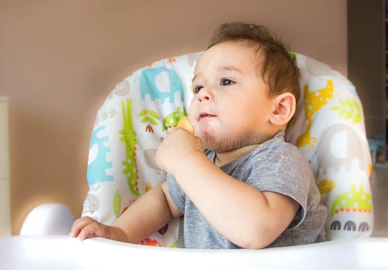 Den gulliga ståenden behandla som ett barn pojken som äter barnkexet som den första maten för behandla som ett barn 10 månader li arkivfoto