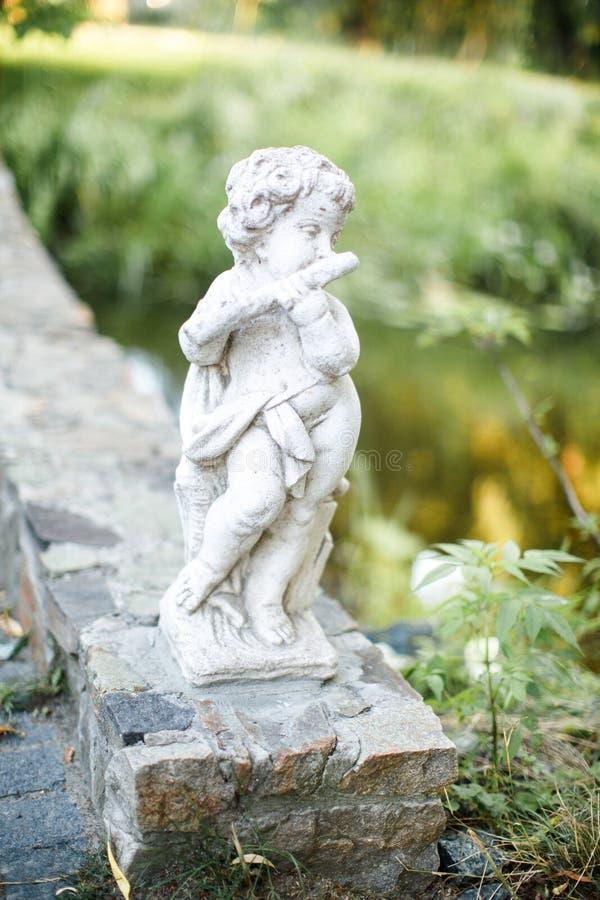 Den gulliga stenstatyn som spelar flöjtinstrumentet i trädgården Angel Sculpture arkivfoton