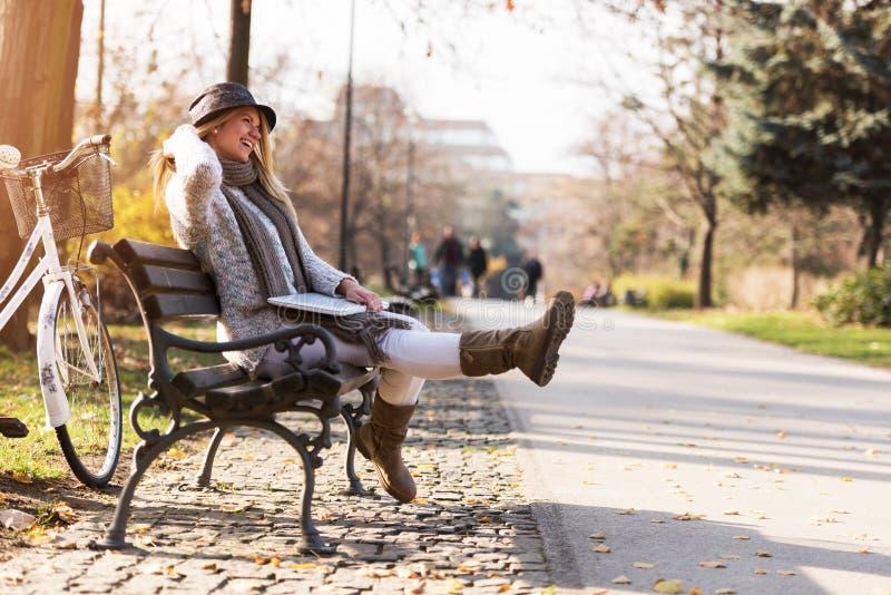 Den gulliga studentflickan med hatten parkerar på bänken som arbetar på bärbara datorn arkivbild
