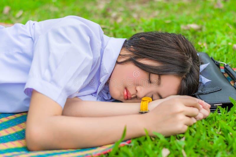 Den gulliga thailändska skolflickan faller sovande på det mattt under att göra som är utomhus- arkivbild