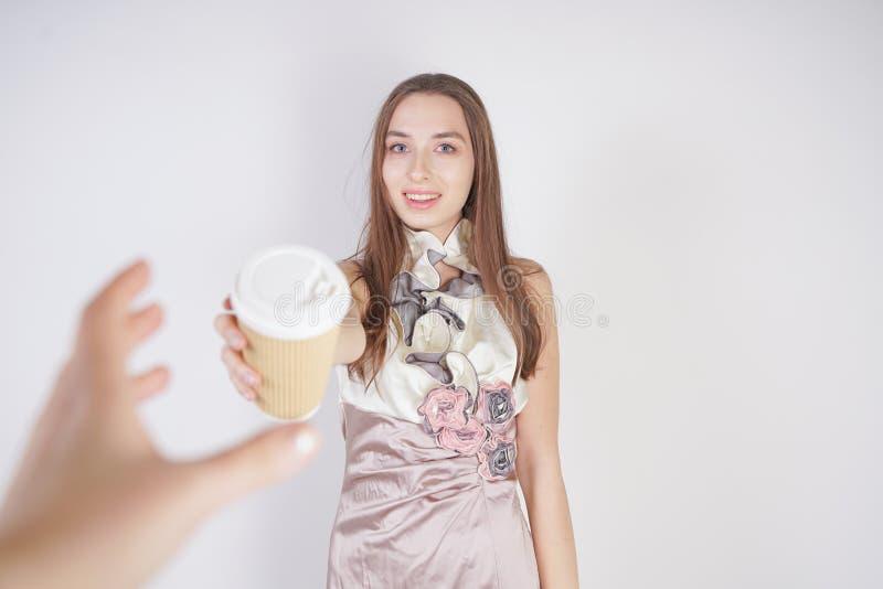 Den gulliga tonåriga caucasian flickan i en nätt aftonklänning ger en pappers- kopp kaffe som behandlar interlokutören och le arkivbild
